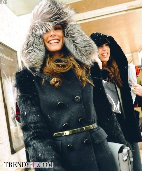Оливия Палермо в черном пальто и шапке-ушанке