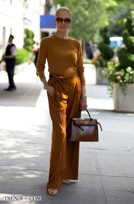 Пятидесятилетняя женщина в широких брюках и тонком свитере