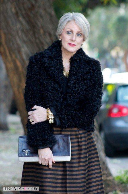 Женщина 50-ти лет в черном полушубке и полосатой пышной юбке