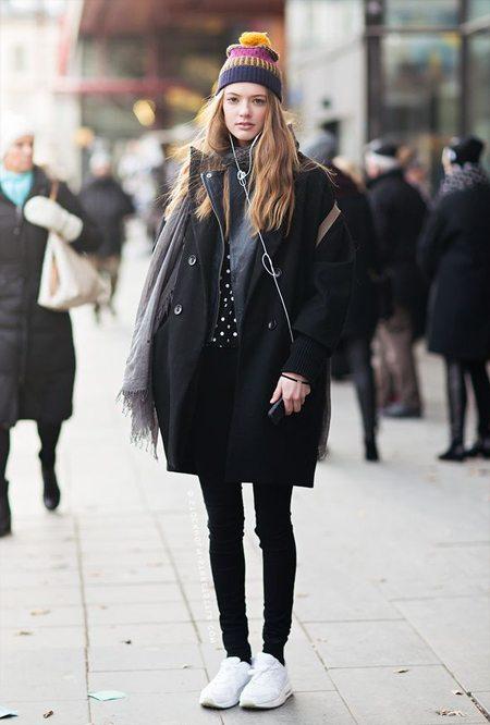 Девушка в разноцветной вязаной шапке с помпоном и в пальто