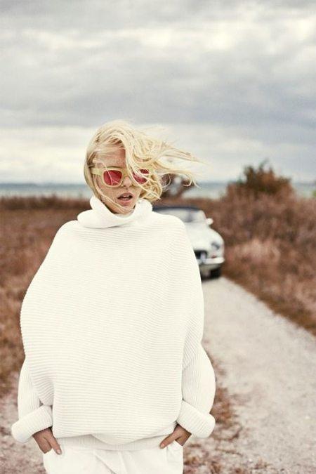 Белый объемный свитер в сочетании с белыми брюками