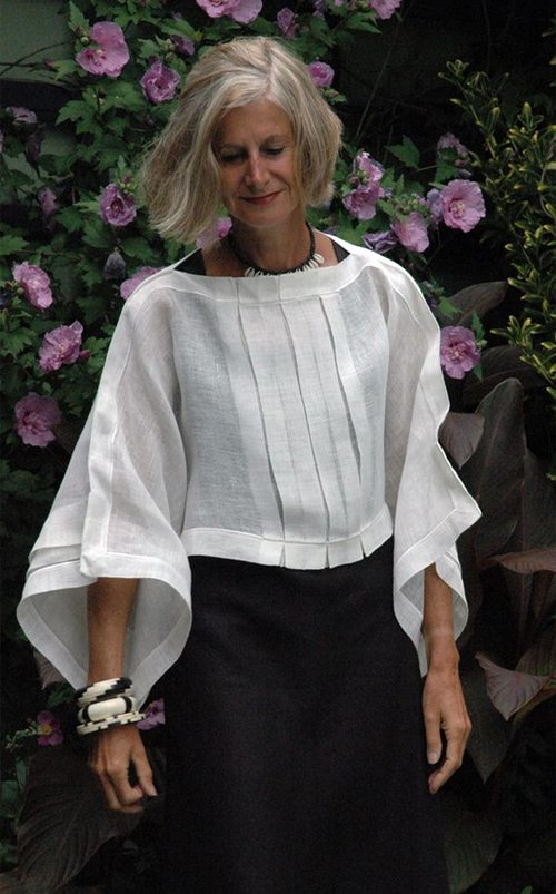 Белая блузка с рукавами типа колокол на женщине среднего возраста