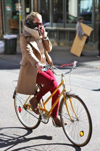 Уличная модница едет по городу на велосипеде