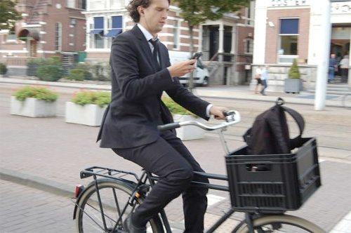 Бизнесмен в хорошем костюме на простейшем велосипеде