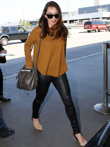 Эмилия Кларк в обтягивающих черных брюках и коричневой разлетайке