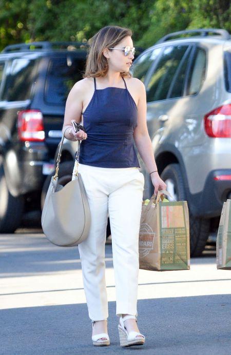 Уличный стиль Эмилии Кларк. Белые брюки и синий топ.