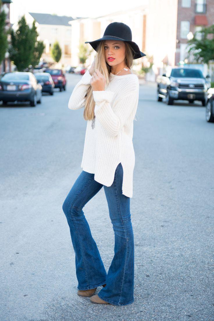 Голубые расклешенные джинсы и белый удлиненный свитер