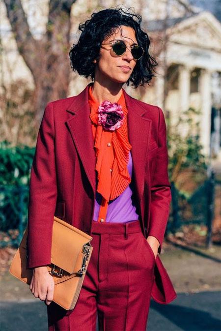 Ясмин Сьюэлл в блузке цвета ультрафиолет и в бордовом костюме
