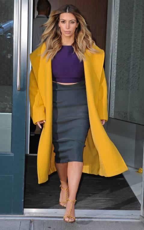 Ким Кардашян в фиолетовом топе, серой юбке и желтом пальто