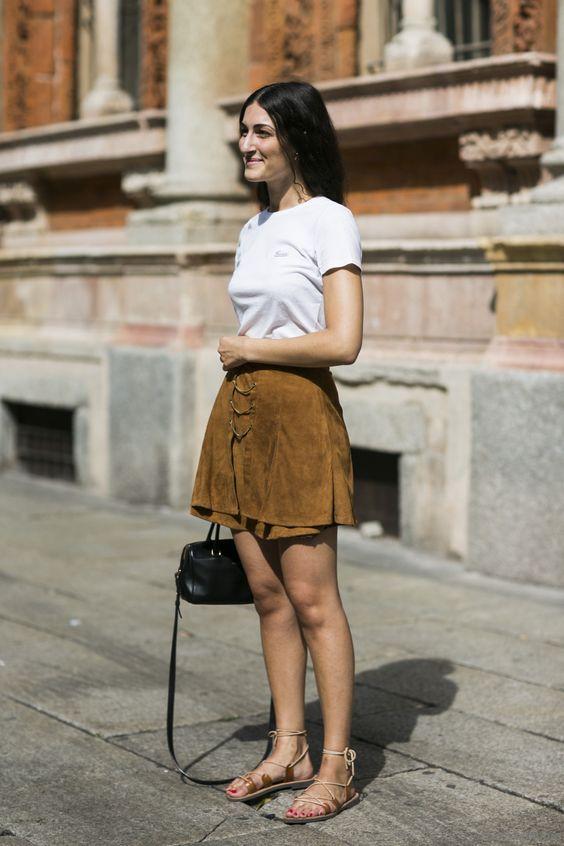 Замшевая коричневая юбка, белая футболка и сандалии с переплетениями