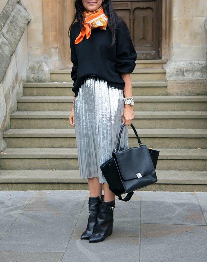 Серебристая плиссированная юбка с черны свитером и черными сапогами