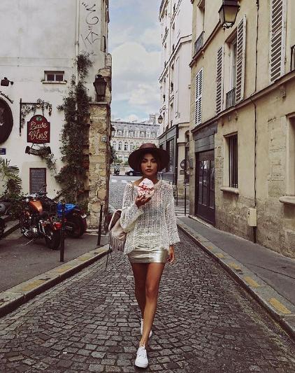 Короткая юбка цвета металлик с прозрачной кофтой и белыми кедами