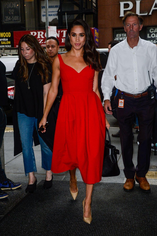 Актриса Меган Маркл в ярко-красном платье длины миди