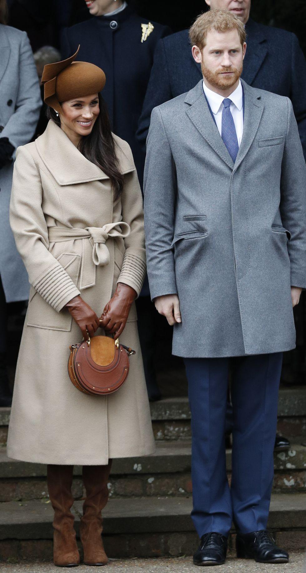 Меган Маркл в коричневой шляпке и с круглой сумкой