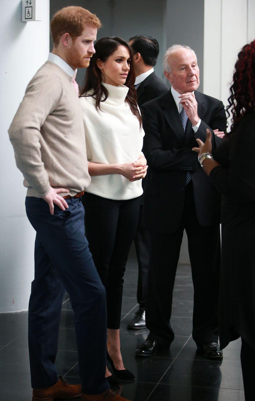 Меган Маркл в белом свитере, черных брюках и черных туфлях