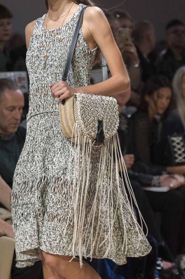 На фото модная женская сумка с плетеной крышкой и бахромой