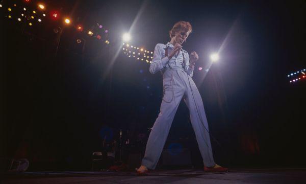 Дэвид Боуи в голубых штанах с подтяжками и голубой рубашке
