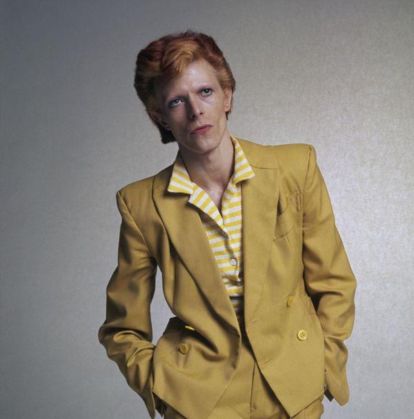 Рок-певец Дэвид Боуи в желтом костюме