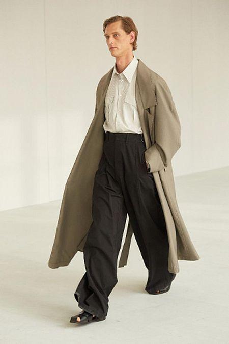 Объемный мужской плащ, белая рубашка и широкие черные брюки