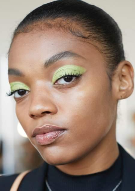 Макияж с зелеными тенями, подкрученными ресницами и бесцветным блеском для губ
