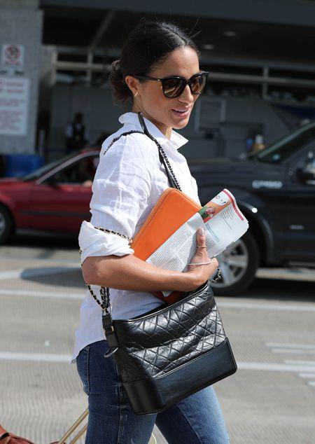Меган Маркл в джинсах и белой рубашкой с черной сумкой Chanel