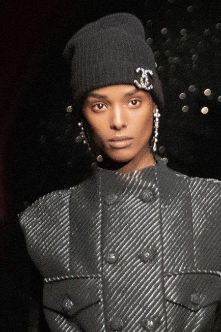 Черная вязаная шапка с брошью в виде знака Chanel