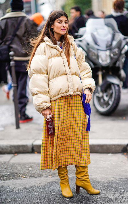 Светлая дутая куртка, желтая юбка в клетку и горчичные сапоги