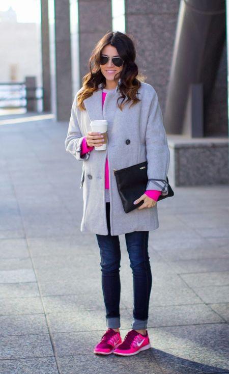Розовые кроссовки, узкие темные джинсы, розовый свитер и серое пальто