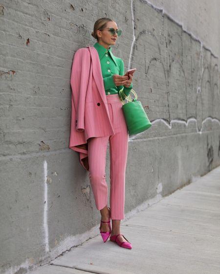 Розовый брючный костюм, зеленая рубашка и зеленая сумка