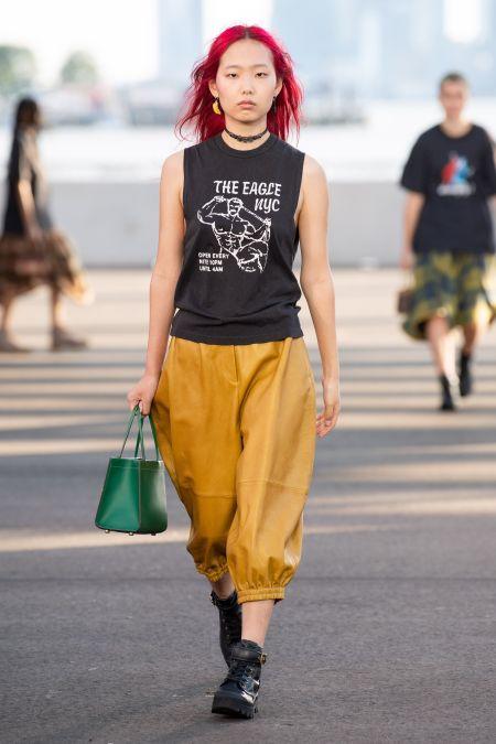 Зеленая сумка в сочетании с желто-оранжевыми объемными брюками