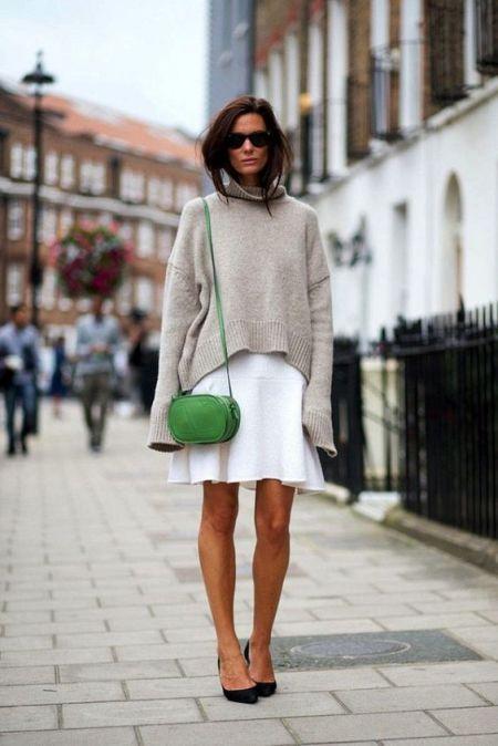 Зеленая овальная сумка-кроссбоди, бежевый свитер и белая юбка